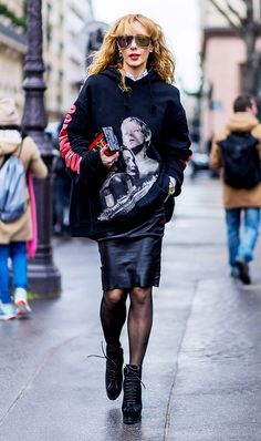 Elina Halimi dresses up her Vetements hoodie with a leather skirt, sheer tights and a Louis Vuitton clutch