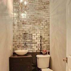 Add mirrored tiles to windowless rooms. I adore this idea for a small bathroom!