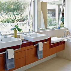 Fasten towel bars under sinks for a streamlined look that won't interfere with the bathroom's view. | Coastalliving.com