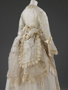 Bustled Wedding Dress - Silk gauze, trimmed with silk embroidered net lace, silk satin, and lined with silk - English or French - Worn in England by Lucretia Crouch, who married Benjamin Seebohm at the Friend's Meeting House in Clevedon, 10 September 1874 - Back View