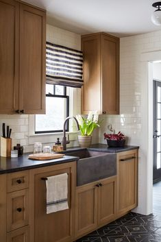 In this image top: Bosch Panel Ready Dishwasher, $1,899; Farmhouse Kitchen Sink, Native Trails, $1,698; Pull-Down Kitchen Faucet in Oil Rubbed Bronze, Newport Brass, $1,039.