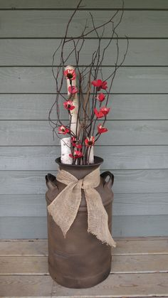 A friend gave me this old milk can. I sanded it, sprayed it flat black and then sprayed a textured autumn brown on it. Lightly sanded in a couple of areas, placed a flower arrangement and a burlap ribbon. A weekend project, Love it! Old Milk Jugs, Milk Cans, Country Decor, Rustic Decor, Antique Milk Can, Milk Can Decor, Burlap Ribbon, Floral Arrangements, Flower Arrangement