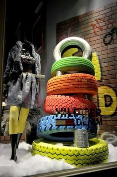 Good use of recycled elements in the window - old tires painted in bright colors Mais Christmas Window Display, Window Display Design, Store Window Displays, Retail Displays, Denim Window Display, Visual Merchandising Displays, Visual Display, Retail Windows, Store Windows