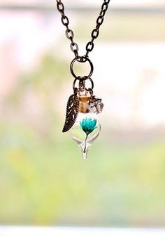 Miniature glass bottle terrarium necklace with a real dried teal flower inside and a filigree leaf and genuine crystal element dangling
