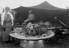 A cook stands next to one of a number of copper serving trays, six feet in diameter, filled with rice and meats for a feast to be enjoyed by Emir Abdullah I of Transjordan and King Ibn Saud of Saudi Arabia on August 17, 1935.