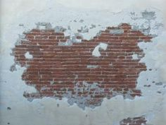 Red brick wall with worn surface partly covered in thin, white concrete.