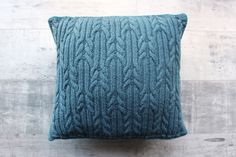 This square hand knitted cushion has been made using teal and grey acrylic yarns. The front is a beautifully intricate mix of bands of cable and rib stitch. The back has the soft textural qualities of Moss Stitch.This cushions clean colour combination would complement a wide variety of interiors, kitchens, living rooms or bedrooms. Whether scattered across a sofa or nestled in an armchair, it will enhance the appearance of any room. . Materials Yarn: Womens Institute Premium Acrylic Yarn…