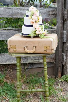 Rustic Wedding Cake with Navy Ribbon and Pink Flowers Perfectly Placed on top of a Pink Suitcase