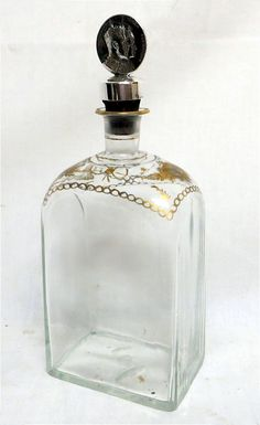"DECANTER with STOPPER English Ca. 1740-1760 Blown bottle with German half-post. Open pontil. Crystal glass with gold leaf floral decoration. Size: 8"" high x 4"" wide x 3"" deep."