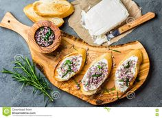 Photo about Toasted bread bruschetta with cream cheese and garlic edible flowers on olive wooden cutting board on stone slate gray background. Image of closeup, cooking, bread - 82029188 Olive Boards, Sandwich Cream, Edible Flowers, Bruschetta, Fresh Rolls, Garlic, Sandwiches, Cheese, Cooking