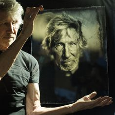 Roger Waters of Pink Floyd with his portrait on glass, by Giles Clement