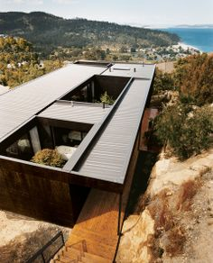 Modern hillside home with stained plywood cladding
