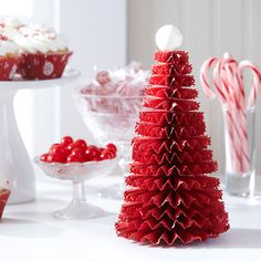 """Red Paper Christmas Tree--cut 2-1/2X12"""" red cardstock, continue w/2-12' that are 1/8"""" narrower than 1st, score crosswise 1/2"""" apart. Scallop punch one edge. Use clear-drying glue to adhere short ends; squeeze medllion together and secure with hot glue. Glue a ball ornament to top."""