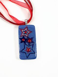 Beautiful blue and red stars with Swarovski red crystals in the middle on the domino pendant.  $23.00  Like me on Facebook (wiredboutique) for a discount coupon!