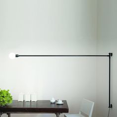 POTENCE PIVOTANTE Embossed wall lamp. Body in aluminium and metal, painted matt black. Diffuser is a opal glass bubble. Arm fixed to the wall and rotating to the horizontal axis, describing a 180° corner. Power cable with plug and dimmer.