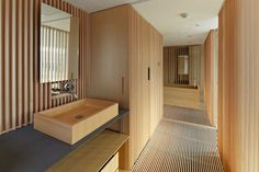 A very modern take on traditional Japanese design and materials...interior sink and cabinetry design leading to the bathroom in frame right...