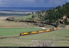 With stormy weather over the plains and the city of Denver (visible just above the tree line on the ridge) in the background, a westbound Union Pacific manifest freight climbs out of Clay, Colorado, on April 18, 2003. Leading the eight locomotive consist is a former Chicago and North Western GE AC4400CW.