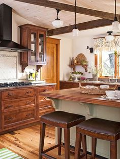 Finely tuned features make this kitchen nearly vibrate with country-style charisma and warmth. Alderwood cabinets set the laid-back tone, while granite perimeter counters and oak on the island create an air of substance. Three kinds of tile add interest to the backsplash, while handcrafted corbels support the island with shapely appeal. Hammered nailheads trim leather seats on the stools for the finishing touch./