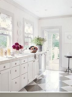 White cottage kitchen with grey and white checkerboard floor.