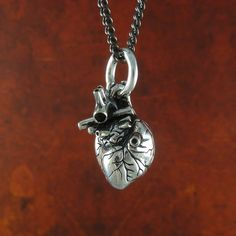 Small Antique Silver Anatomical Heart Necklace by Lost Apostle. A smaller version of the Lost Apostle anatomical heart necklace, and every bit as detailed. Every aspect of the real thing beating away in your chest is captured in this heart, a true original. A heartbeat, a pulse, a reminder of everything you cherish and everything you hold close. Completely hand-crafted and cast in solid white bronze, with a thick silver plate finish.