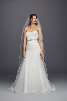 From the sweetheart neckline to the ethereal tulle skirt, this David's Bridal strapless mermaid wedding dress is a study in loveliness. Add personality with a statement sash.