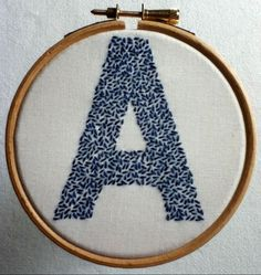 Hand-embroidered letter A sewn in seeding stitch using royal blue thread on white fabric. Embroidery Hoop Decor, Embroidery Alphabet, Wooden Embroidery Hoops, Baby Embroidery, Cross Stitch Embroidery, Embroidery Designs, Diy Art Projects, Yarn Projects, How To Embroider Letters