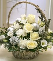 Sparkle. A beautiful Christmas flower basket comprising of cream Roses, white Freesias, Lisianthus and Carnations. Pine Cones and Holly sprigs complete the arrangement.