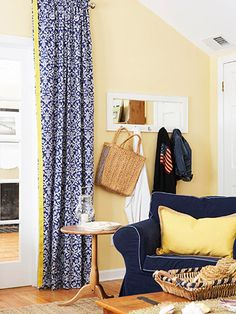 navy couches. raton baskets. neutral floors. yellow pops. maybe a little too yellow with the walls, but pretty color scheme