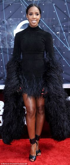 Fuss and feathers: Kelly Rowland displayed her shapely legs in an extravagant black feathered dress, looking like a peacock
