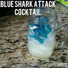 Blue shark attack cocktail containing, rum, pineapple juice, blue curacao, and gummy sharks. Blue Drinks, Mix Drinks, Party Drinks, Cocktails, Alcohol Shots, Liquor Shots, Shark Week Drinks, Blue Shark, Blue Curacao