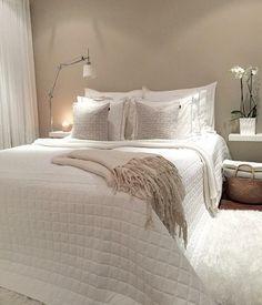 Quarto de casal pequeno, em tons de branco. Para aquecer o ambiente, a parede foi pintada em um tom terroso. ( cama de casal tons neutros decoração)
