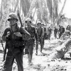 A column of Marines on Tarawa. Note the Marine in the front is carrying a captured Japanese Arisaka rifle. #wwii #ww2 #marine #usmc #tarawa
