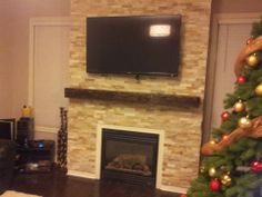 Another fireplace mantel installed just in time for Christmas! We love how you can see the reflection of the stunning ceiling light in the TV! Barn Door Hardware, Fireplace Mantels, Wood Furniture, Beams, Reflection, New Homes, Ceiling Lights, Doors, Studio