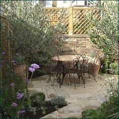 Small space Mediterranean garden design with softly coloured pavers, mirrors behind trellis for extra light and illusion of space, classic planting of olive trees, Italian Cypress, lavender,Verbena bonariensis, roses, clematis, thyme and baby's tears.