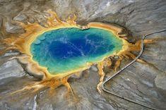 Passarela alucinante (Grande Fonte Prismática, EUA) No centro da Grande Fonte Prismática, um lago termal de 113 metros de diâmetro situado no parque nacional da Yellowstone (Wyoming, Estados Unidos), a água alcança uma temperatura de 93ºC. Conforme se chega à margem, as temperaturas são um pouco mais baixas. E de acordo com a temperatura, vivem diferentes bactérias que contribuem para dar uma coloração diferente à água.