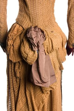 This tan open-weave linen dress, c. 1884, has a corseted bodice trimmed with maroon velvet and metallic beading; the brown faille skirt is draped with matching linen forming a bustle in back and apron...