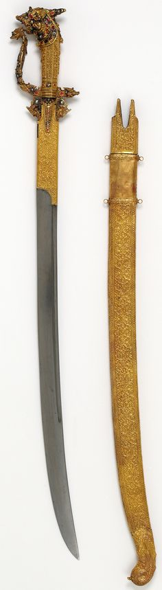 Sri Lankan kastane sword, dragon-headed pommel, steel, chased and embossed gold sheath, Travancore, Kerala, India, 19th century. The kastane is the national sword of Sri Lanka. It typically has a short curved single-edged blade, double-edged at the point. The hilt comprises a knuckle-guard and down-turned quillons, each terminating in a dragon's head. The swords were intended to serve as badges of rank; the quality of ornamentation depending on the status of the wearer. V&A Museum