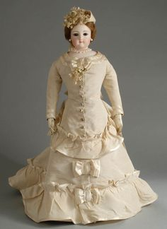 Gaultier fashion doll, ca 1870, wears antique silk faille gown featuring a bustled back and trimmed throughout in fancy silk buttons, ruffles and bows. With a floral bonnet and she wears antique under clothing, leather boots and stunning pearl jewelry.