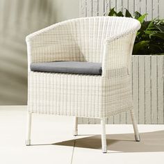 Shop camilla dining-lounge white wicker chair with grey cushion.   Vintage-style seat gets scaled down and made modern in durable faux rattan that stands up to the elements.