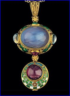 Henry Wilson. Jewelled gold and enamel pendant.  Gold, enamel, sapphire, ruby, emerald, moonstone and pearl. H: 13.4 cm (5.28 in)  W: 5 cm (1.97 in). British, c.1908. Designed in three parts. Concealed behind the central sapphire is a secret hinged compartment. Wilson's ardent mediaevalism is shown to its ultimate expression in this fabulous jewel. Provenance: member of Henry Wilson's family. Sold by Tadema Gallery. Now in the collection of the Indianapolis Museum of Art. View 4.