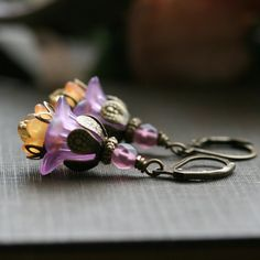Lucite flower earrings in purple and orange. These purple flower earrings are vintage style with antiqued lever back earwires. These flower