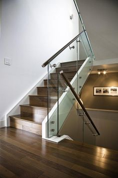 Sleek maple stairs with glass railing and stainless steel handrail