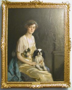 Oil painting on canvas, The Hon. Violet Agar-Robartes (1888-1965) by Richard Jack (Sunderland 1866 – Montreal 1952), signed and dated bottom right: R. JACK. 1914. A three-quarter length portrait of the third daughter of the 6th Viscount Clifden. She is seated to the right and is wearing a pale yellow dress with a long bead necklace and a blue cloak. She is holding a Cavalier King Charles Spaniel on her lap.