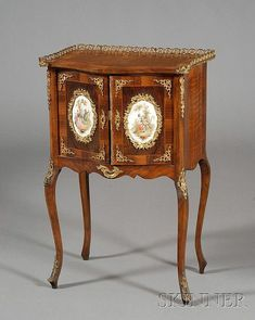 <b>Louis XV Style Brass and Porcelain-mounted Walnut Side Cabinet,</b></i></u> 19th century, with three-quarter brass gallery and serpentine case, fitted with panels of cavorting figures and shelved interior on angular cabriole legs, ht. 31 1/2, wd. 19 1/2, dp. 14 in.