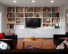 Breathtaking House Design Firms Innovation and Stylish Side: Cozy Family Room Design With Built In Bookshelf And Mounted Wall TV Stand Decorated With Black Leather Sofa And Armchairs At Bailey Residence
