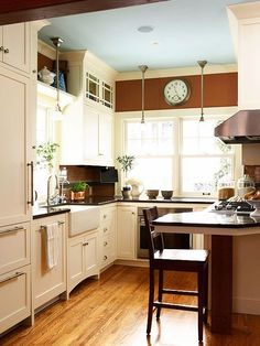 """Get Creative with Paint Kitchens typically don't have a lot of wall space, thanks to cabinetry, backsplashes, windows, and doorways. Use limited wall space as a chance to display a color you might not otherwise choose for a large wall or whole room. Here, a sable brown colors the space above the windows, which grounds the light kitchen. Also, look to the """"fifth wall"""" of a room -- the ceiling -- as a place to add color with paint."""