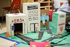 Kindergarten students create their community out of recycled materials and wooden blocks in a reggio-inspired STEM activity