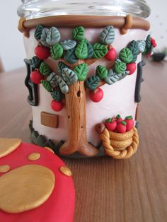 Use polymer clay to build a house around a jar. apple tree outside house.