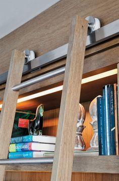 15 estantes para pôr a vida em ordem - Feita de madeira savana, a estante (Marcenaria Visoma) recebeu lâmpadas fluorescentes T5, bem fininhas. A escada desliza em roldanas de aço. Chaise da Novo Ambiente e banqueta do Empório Beraldin.