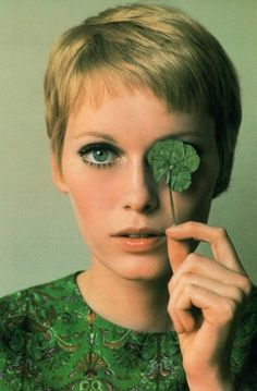 Green Clover Covering one eye. Love the different shades of green from eyes, clover leaf to green top. Mia Farrow